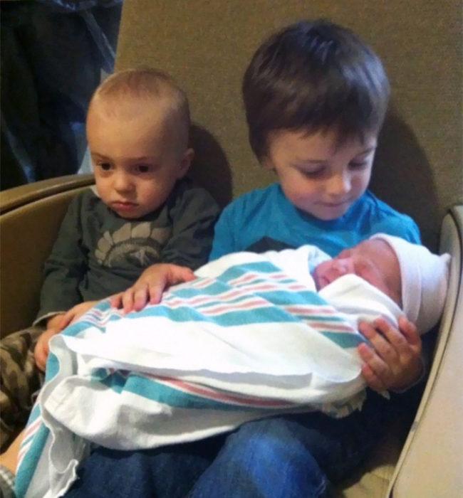 hermano mayor cargando a su hermano mientras el de en medio tiene un semblante triste