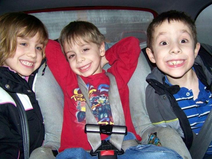 tres niños en un carro