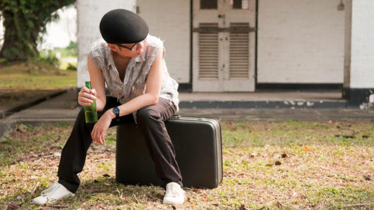 joven fuera de casa sentado en una maleta