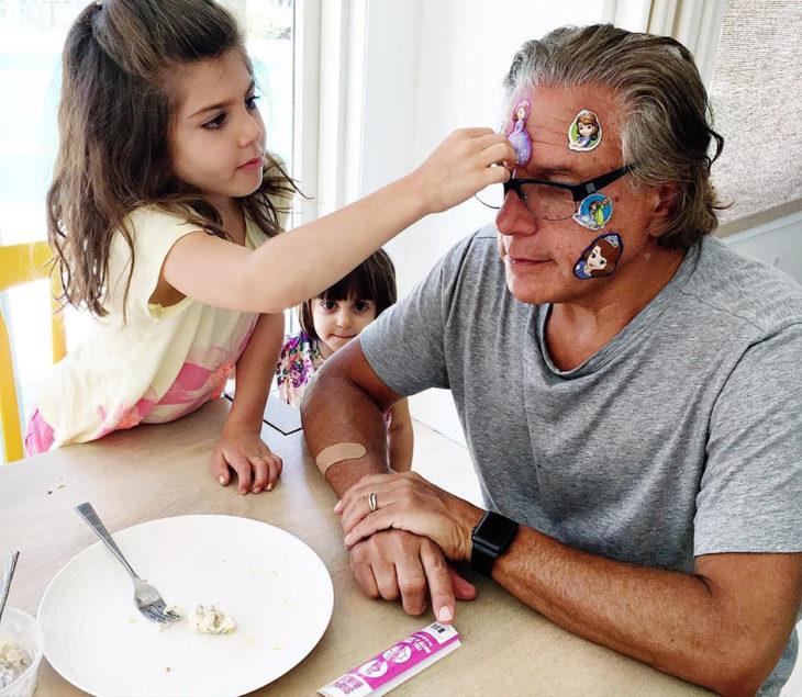niña pegándole un sticker a un hombre en la cabeza