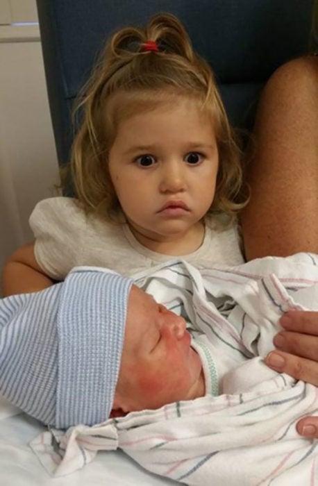 niña sorprendida cuando le dan a cargar a su hermanito