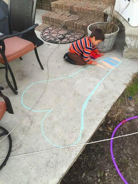 niño dibuja un corazón en el suelo que parece un símbolo fálico