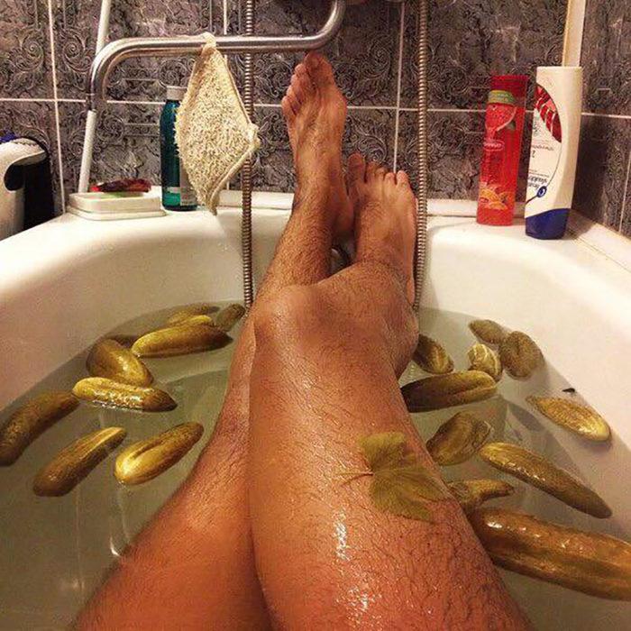 piernas belludas en una tina con pepinos