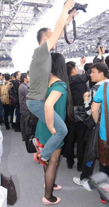 mujer cargando a un hombre que sostiene una cámara