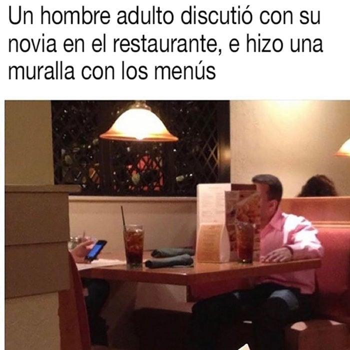 hombre hace un fuerte con los menús del restaurante