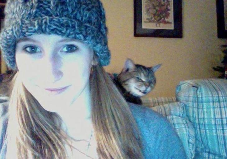 mujer con gorro se toma una selfie y al fondo se vve un gato malvado