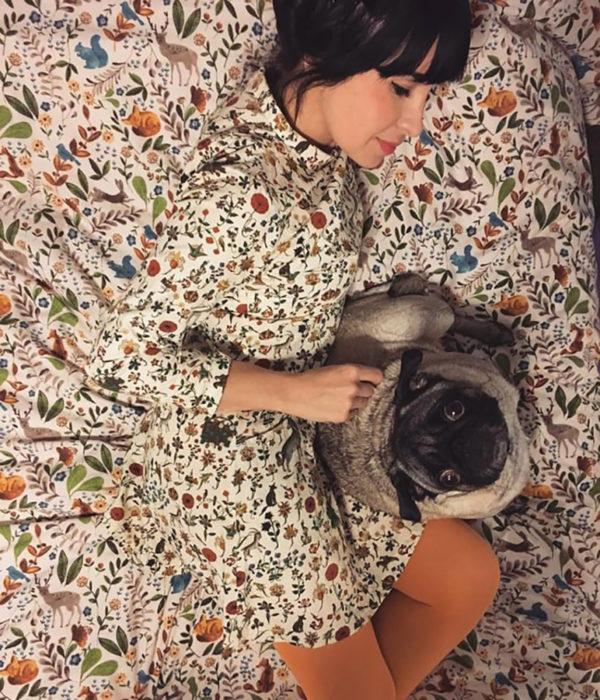 mujer camuflada con las sábanas acaricia a su perro