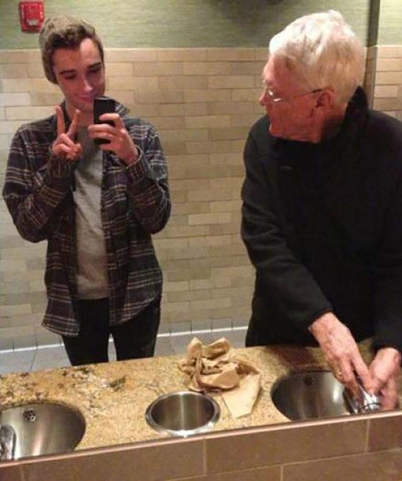 muchacho se toma selfie en el baño y al lado un ansiano lo ve raro