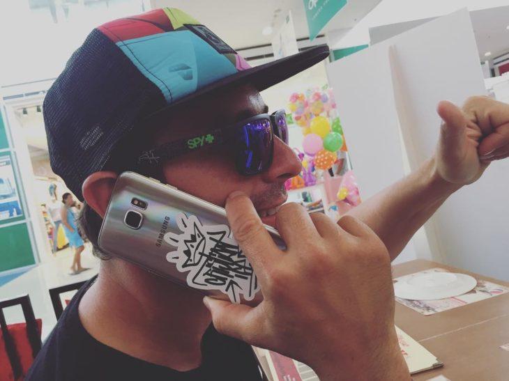 chico con cachucha hablando por celular