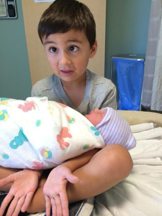 niño haciendo bizcos mientras sostiene a un bebé