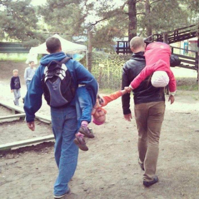 papás cargando a niños que se están dando la mano