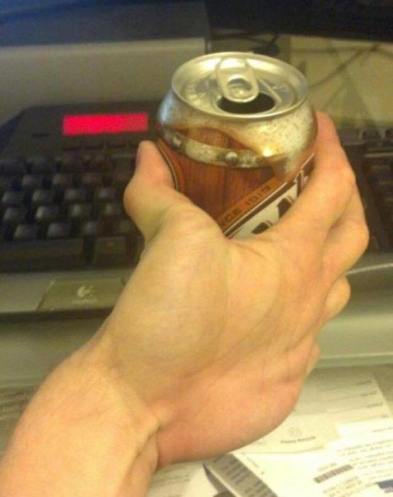 mano volteada sostiene una lata