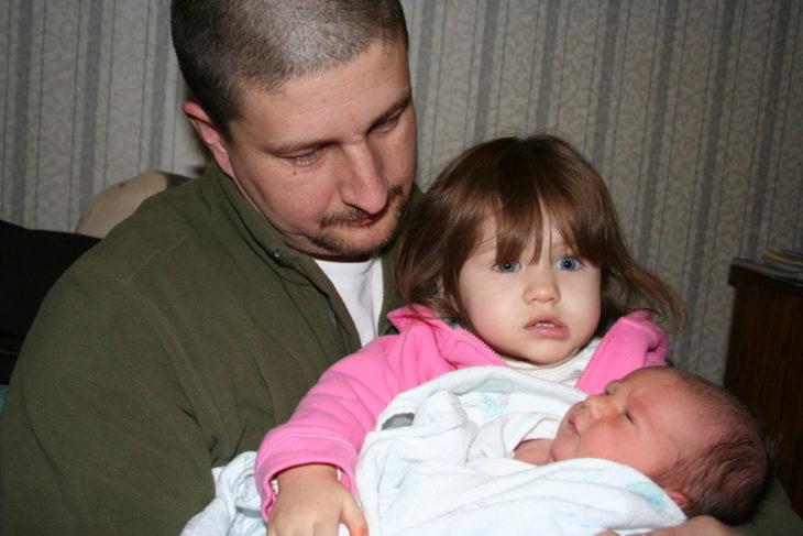 padre carga a su hija que a su vez carga a la bebé recién nacida