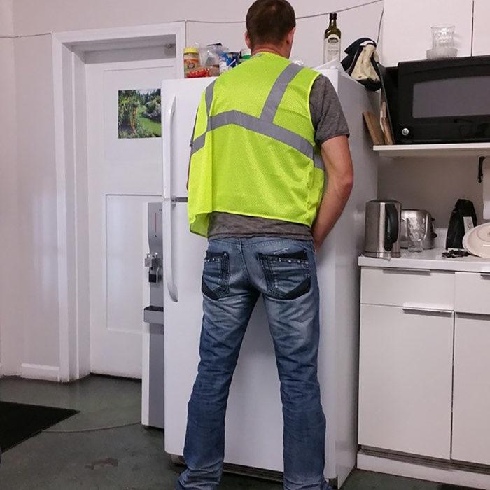 hombre con chaleco fluorescente tratando de orinar en un refrigerador