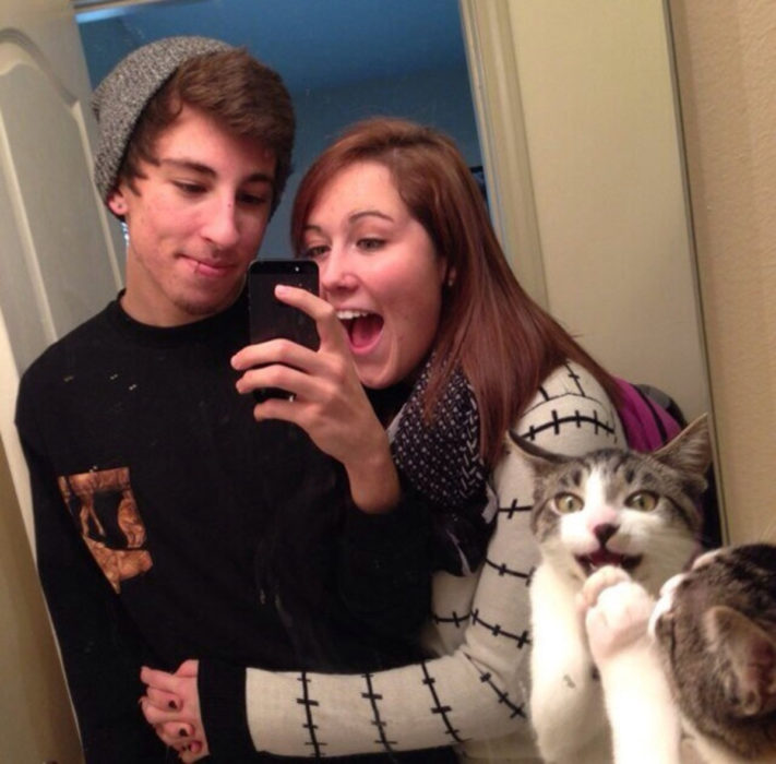 pareja tomándose una foto mientras un gato se ve en el espejo