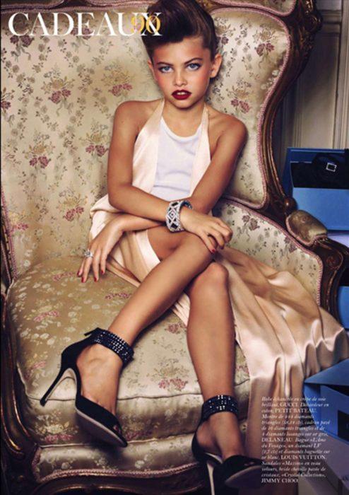 niña con tacones y los labios pintados rojos sentada en un sofá