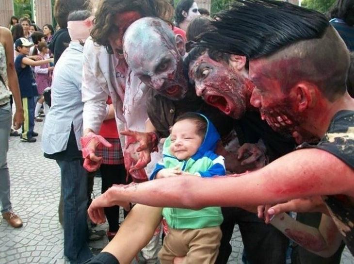 bebé en medio de personas vestidas de zombies