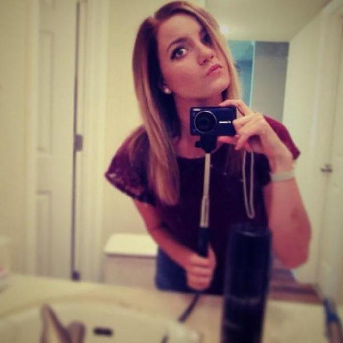 mujer usando un selfie stick con una cámara digital