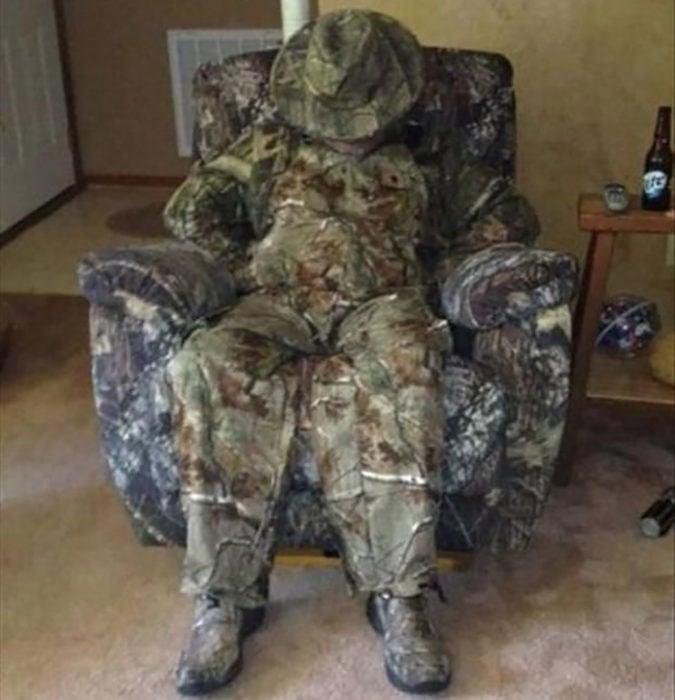 hombre vestido de camuflaje sentado en un sillón camuflado