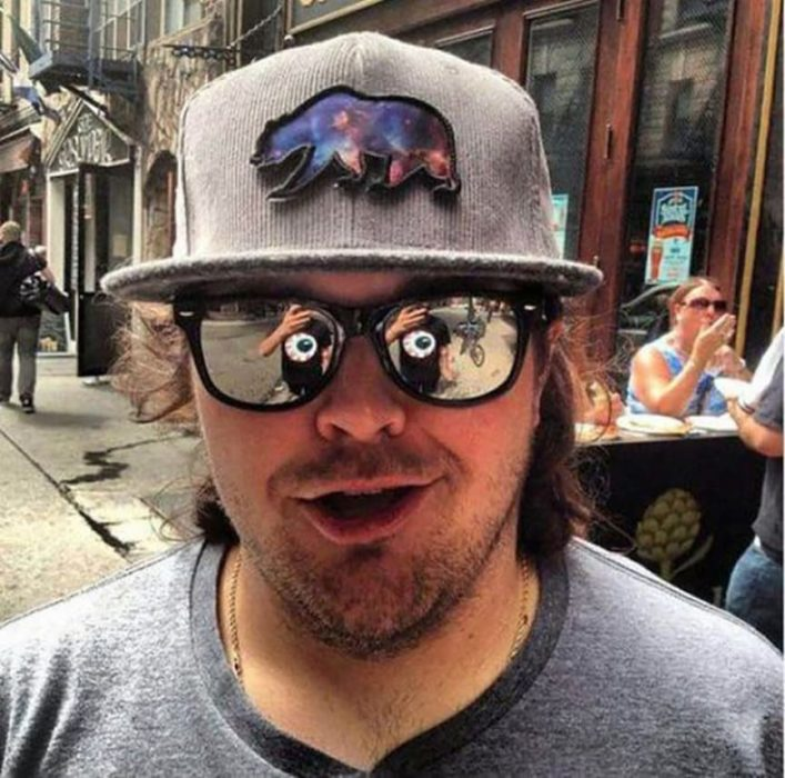chico en cuyos lentes se refleja la camiseta con estampado de ojo de otro chico