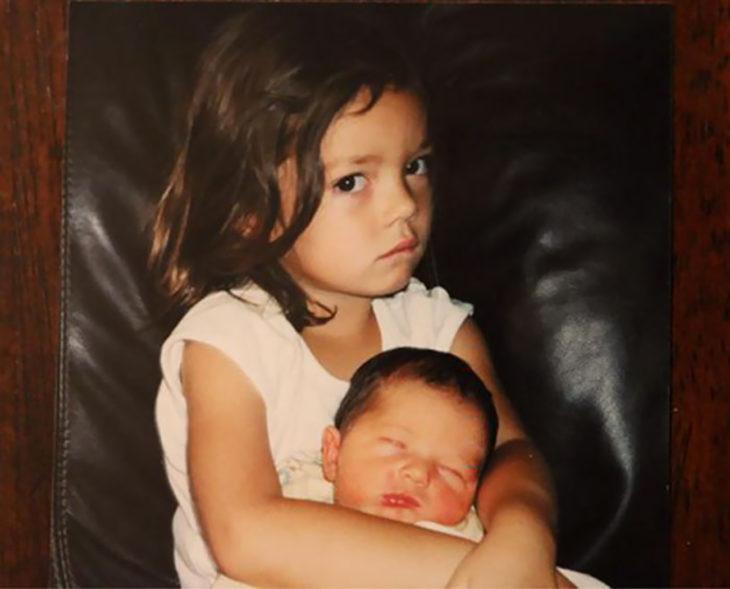niña molesta cargando a un bebé