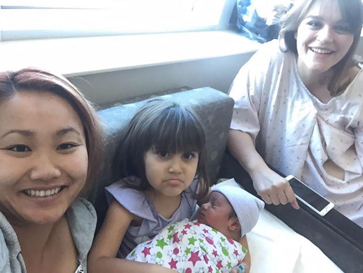 dos señoras sonriendo mientras niña carga a su hermanito recién nacido