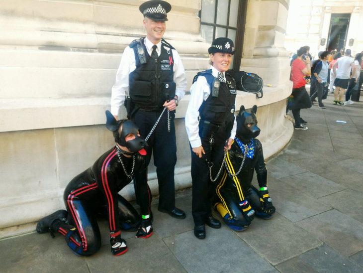 dos policias con correa atada a dos humanos vestidos de perros