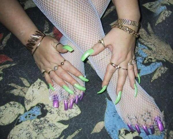 mujer con uñas de los pies moradas, de las manos verdes, y medias de red blancas en las piernas