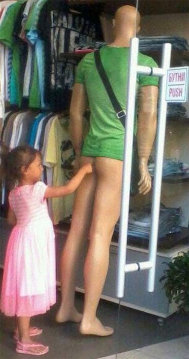 niña toca el trasero de un maniquí masculino