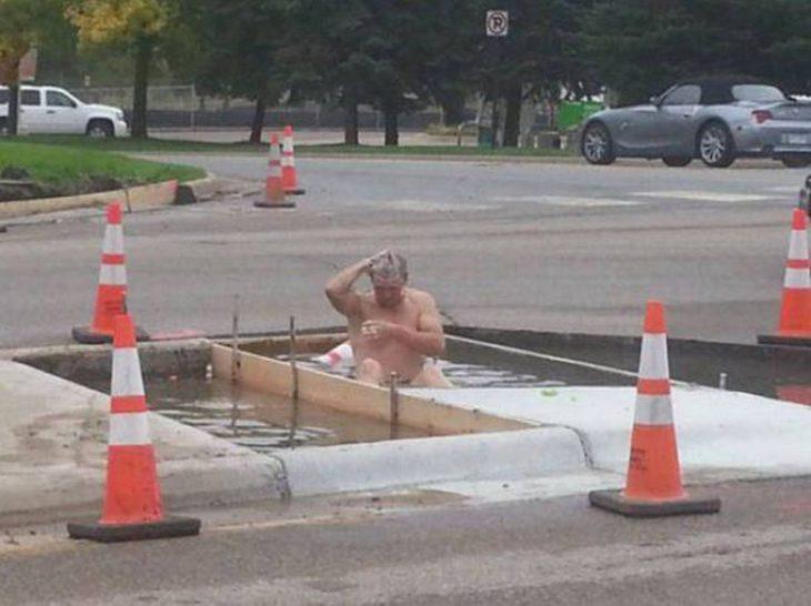 hombre bañándose en un charco de agua en la calle