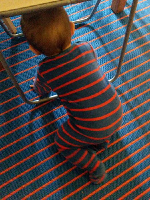 bebé vestido a rayas se camufla con el piso