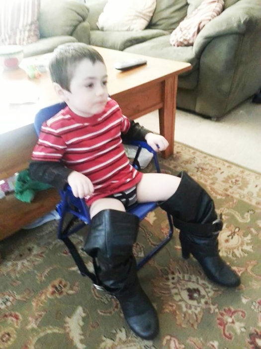 niño sentado usando botas de mujer