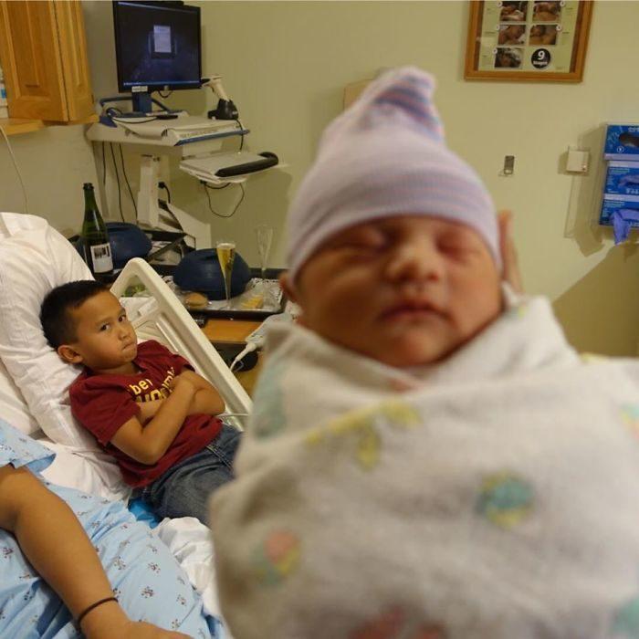 niño cruzado d emanos en ujna camilla molesto mientras la cámara enfoca a un recién nacido