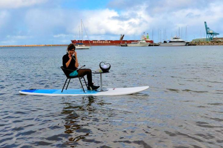 mujer contestando el teléfono en una tabla de surf