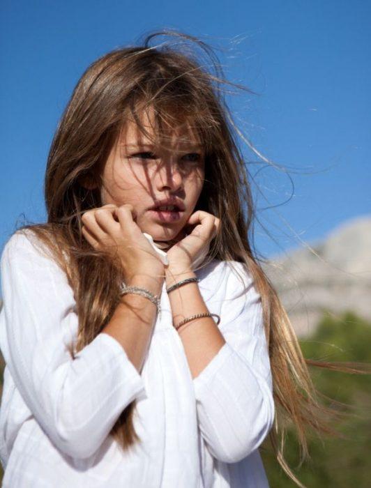 niña tomándose el rostro en un paisaje