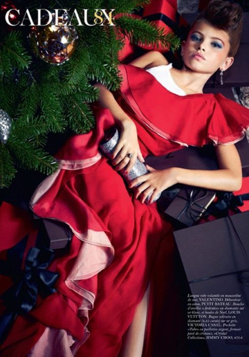niña maquillada recostada con un vestido rojo puesto