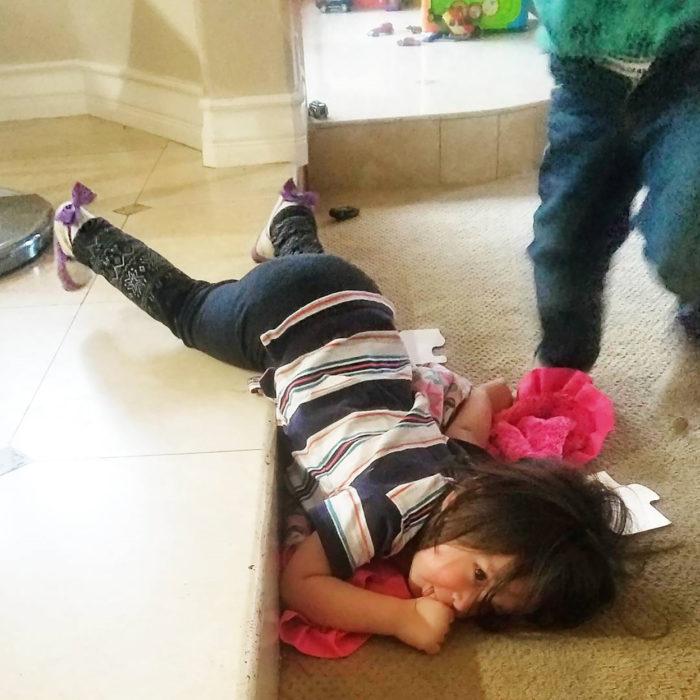 niña en posición rara en el suelo
