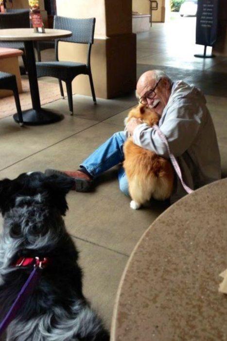 señor abrazando a un perro