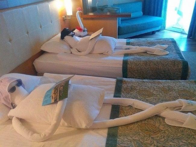 cuarto de hotel con figuras hechas con almohadas