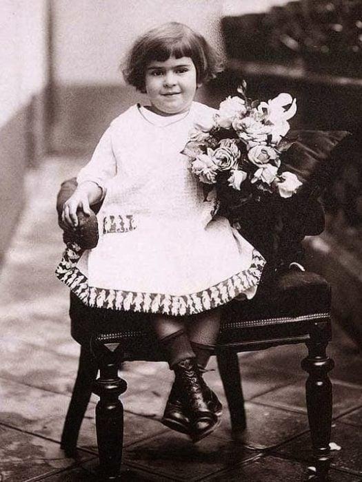 Frida Kahlo de niña sentada en una silla con flores en la mano