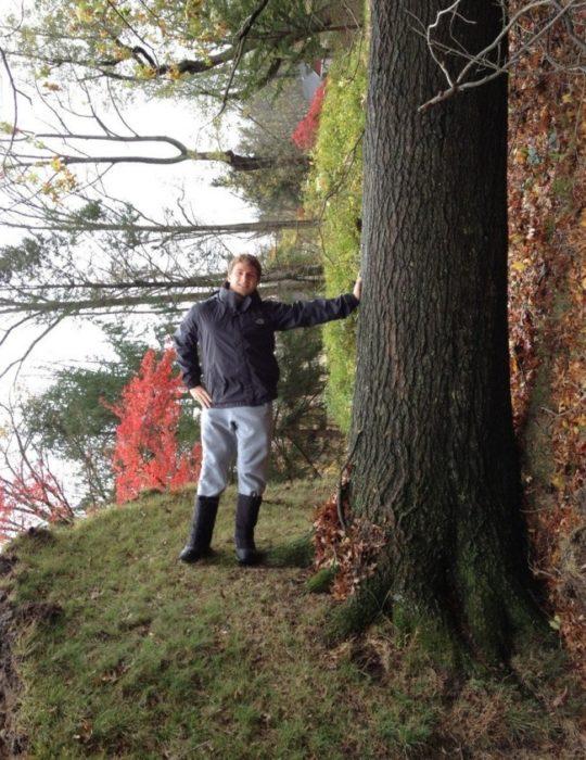 hombre recargado en un tronco pero todo el bosque está acostado