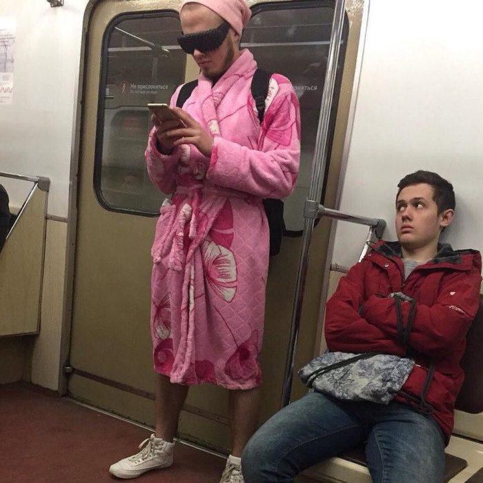 hombre con bata rosa en el metro