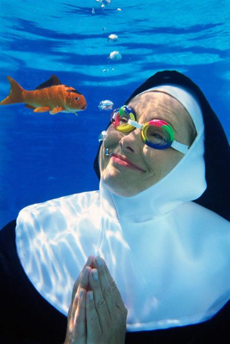 Imágenes inexplicables - monja abajo del agua con googles mientra ve un pez