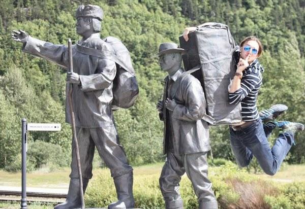 hombre colándose al viaje de dos estatuas