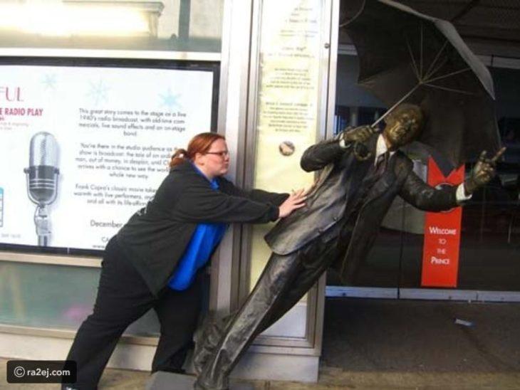 Mujer empujando estatua inclinada