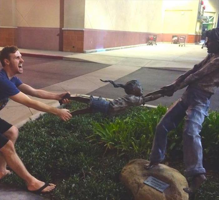 Hombre jugando con estatua