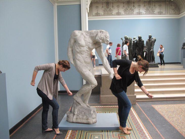 Chicas bailando con estatua de museo