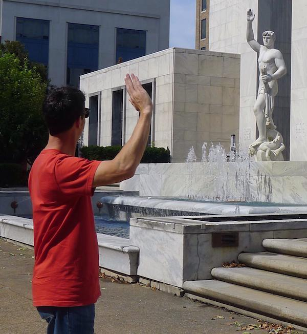 Hombre saludando a estatua