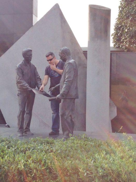 Hombre pidiendo instrucciones a dos estatuas