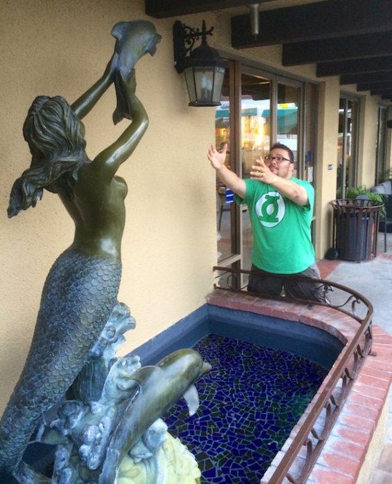 Sirena estatua aventando un delfin bebé y hombre atrapándola